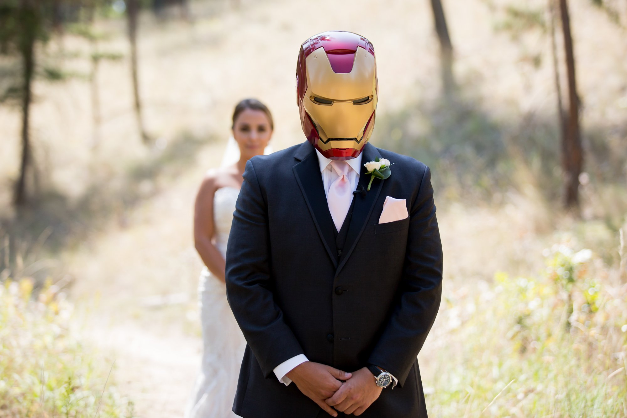A groom wearing an Iron Man mask with his bride behind him