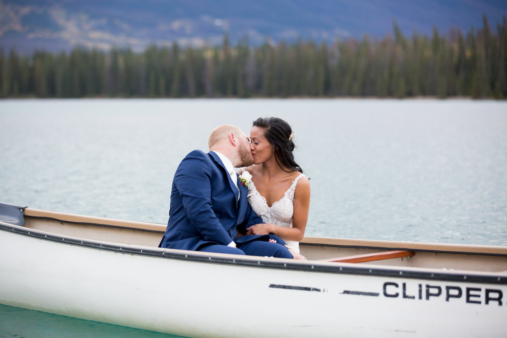 A bride and groom kissing in a canoe