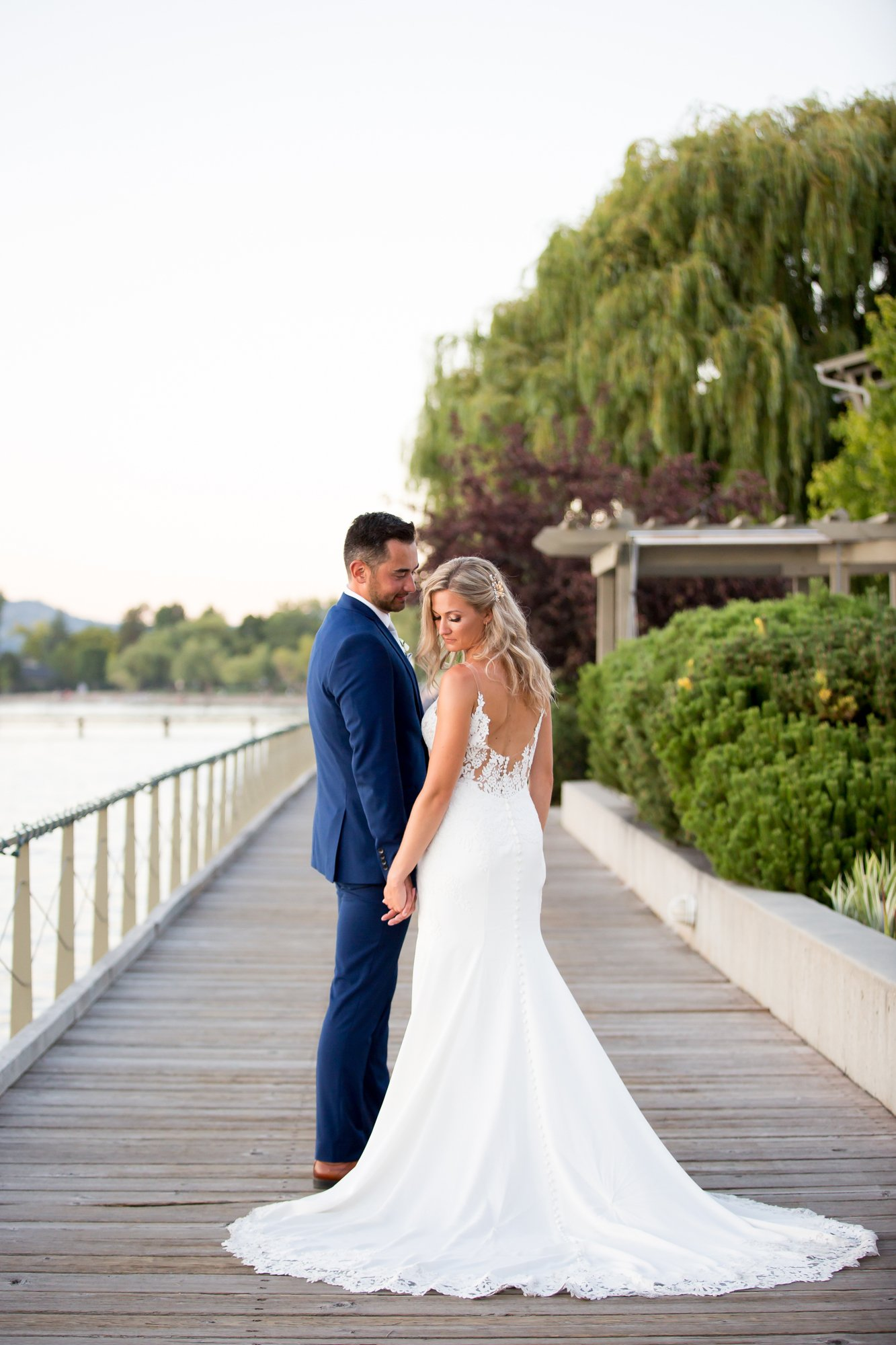 A couple standing together on a dock lakeside