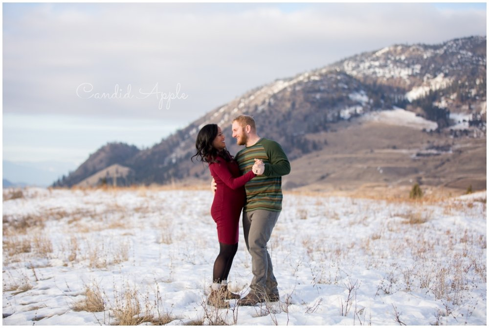 A couple dancing together in the snow while they are expecting their new baby