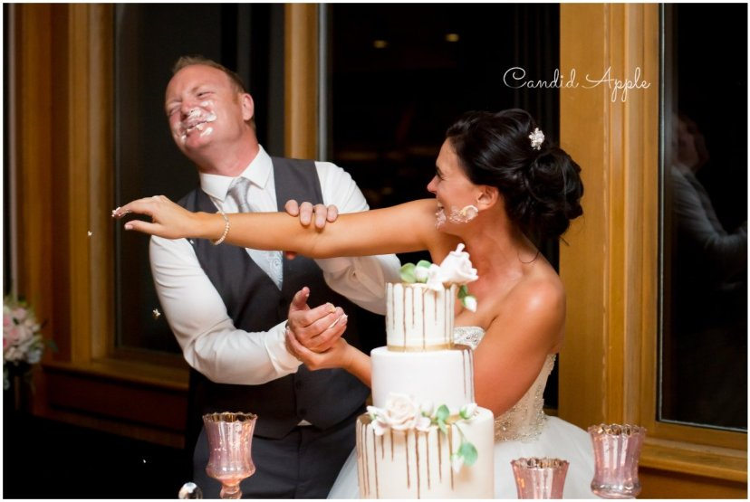 A bride and groom throwing wedding cake at each other