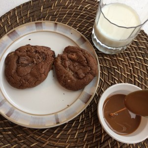 Chocolate cookies on a plate with a glass of milk and creme de leche
