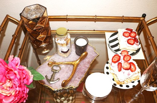 candace rose anderson valentine's day bar cart decorated with an agate cheeseboard, kate spade stripe and polka dot dessert plates and angel food cake, an anchor bottle opener, mercury glass candle, matches, coasters. candieanderson.com