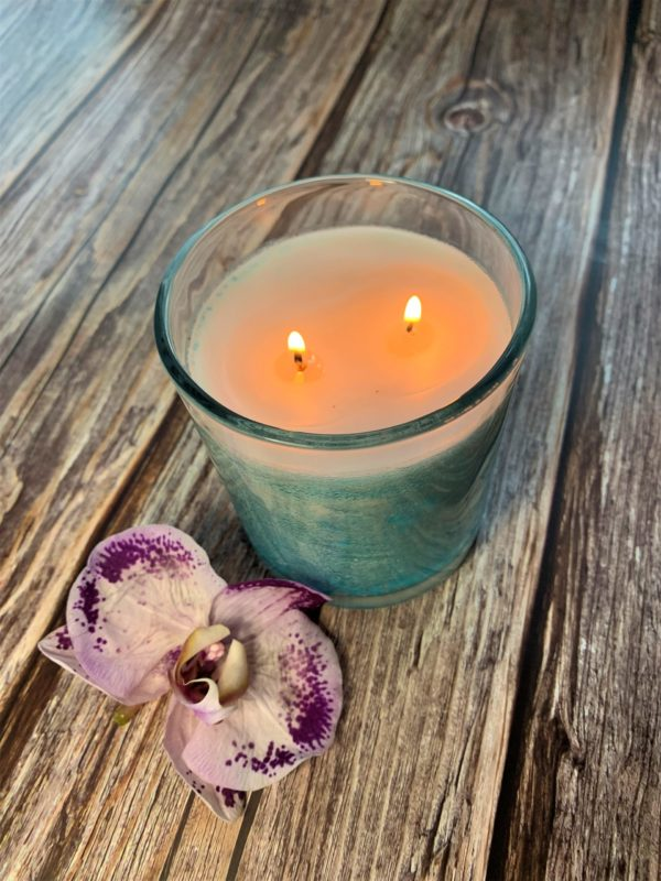beautiful lit white two wick candle with aqua colored sprinkles