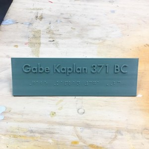 an olive green plastic free-standing nameplate with the name Gabe Kaplan 371BC in raised text on one line and the braille translation underneath