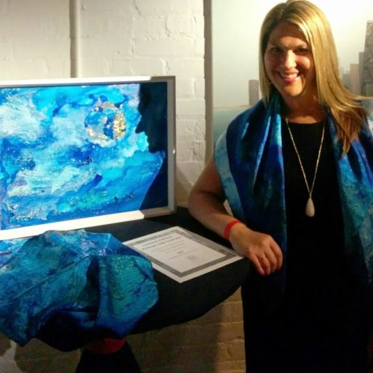 """Becky with Daniel Peress's teal blue abstract painting """"This Too Shall Pass"""", and artisan scarves based on the painting"""