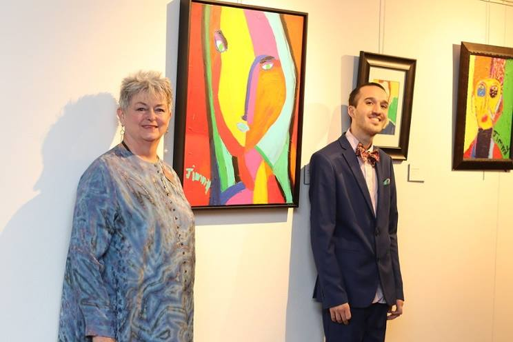 Jimmy Reagan with paintings and a friend