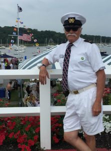 Man stands in front of marina, wearing a yacht club uniform and hat, with a custom made club tie.