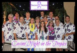 A group photo of a dozen people smiling, wearing flower leis and white and purple Hawaiian shirts made for Tricia's Troops