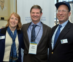 A woman and two men stand together, smiling. The woman wears a blazer and a custom Yale scarf, and the two men wear suits and a custom tie.