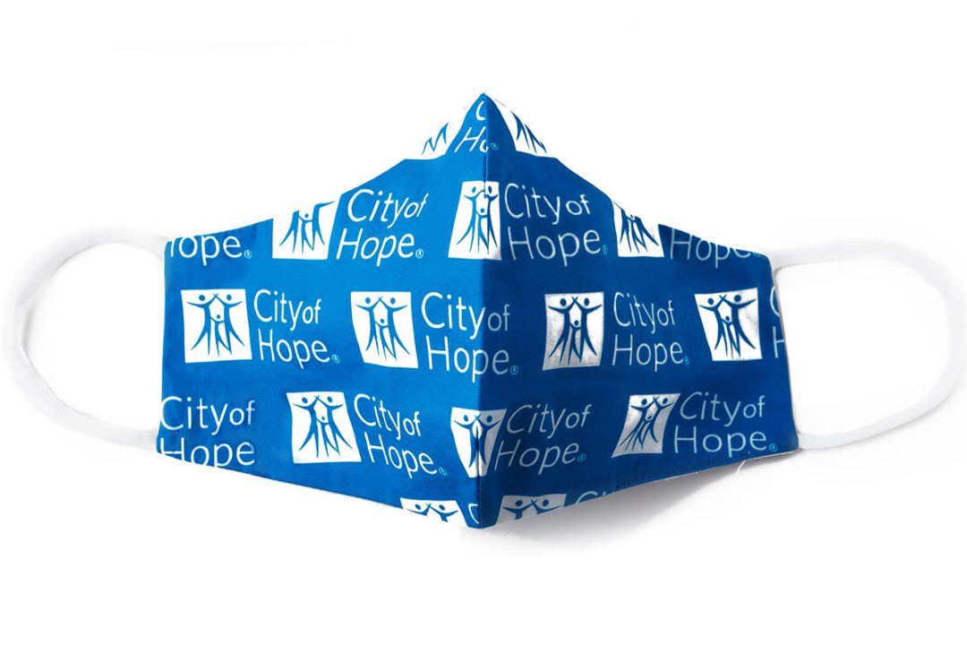 front view of blue custom face mask with white City of Hope logo pattern