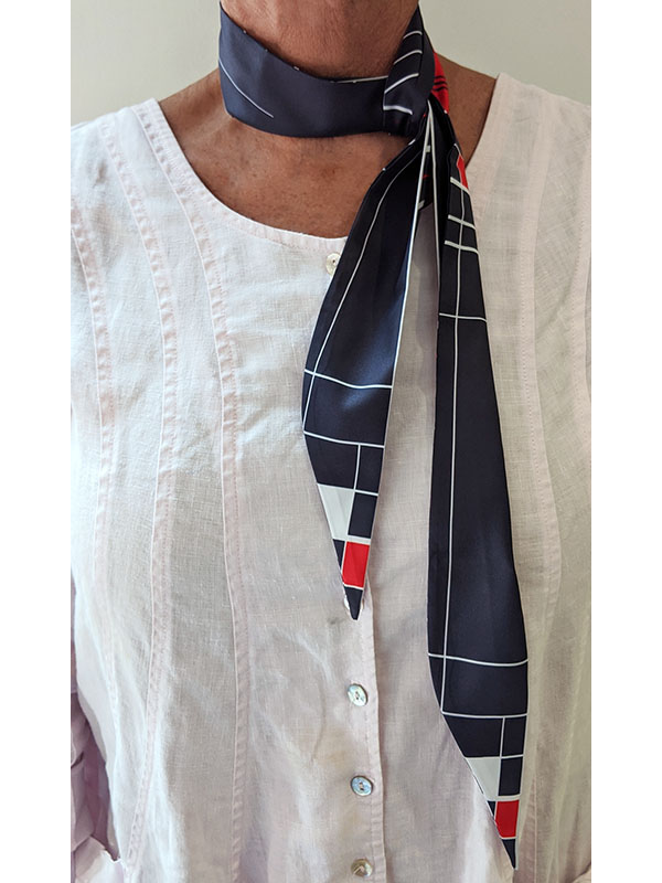 person wearing a custom navy twilly scarf with geometric design