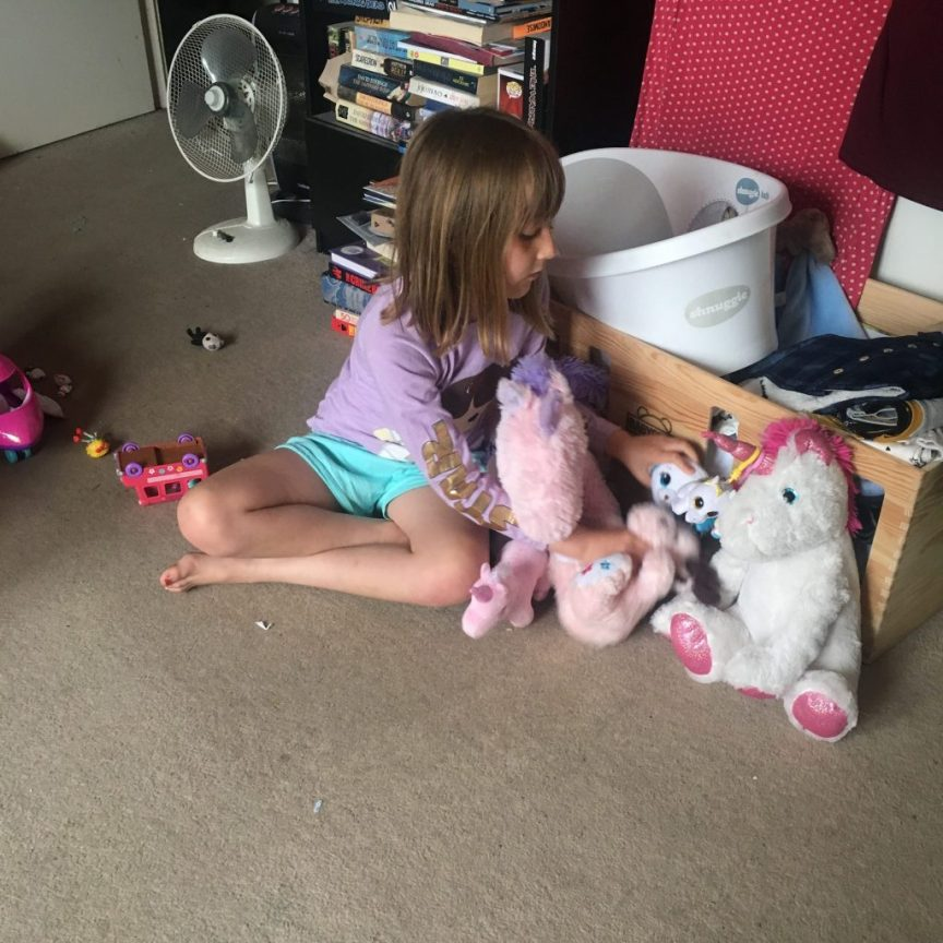 Daughter playing with soft toys and teddies in living room