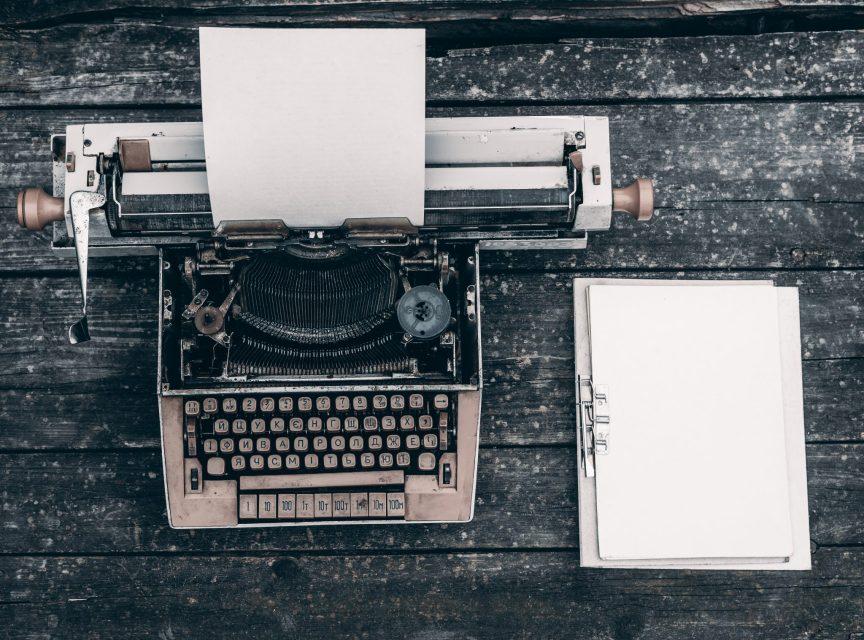 help a child write essays, typewriter and notebook