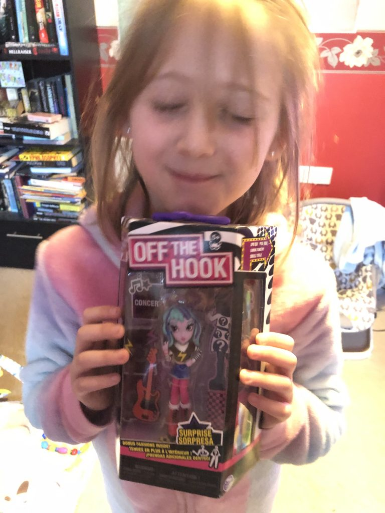 Girl holding boxed off the hook fashion doll