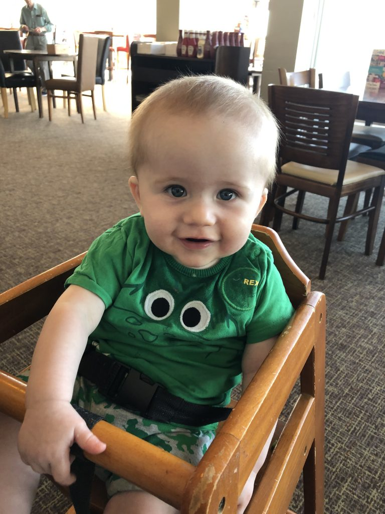 Felix is wearing a green Rex outfit in a wooden high chair at 9 months old