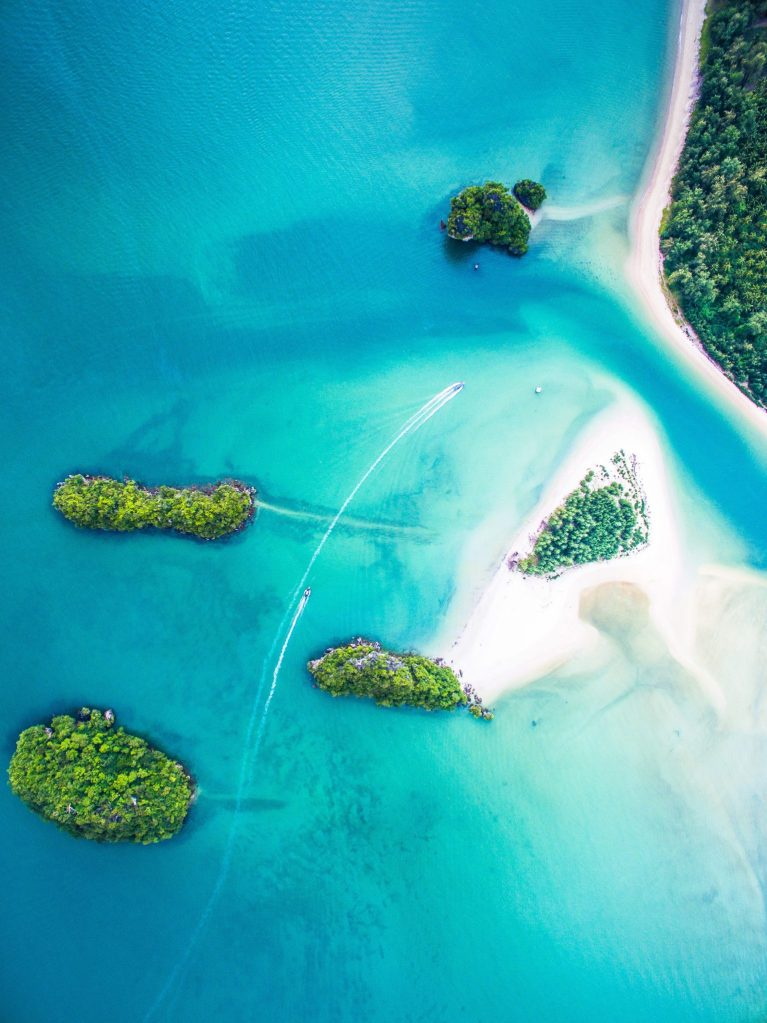 An aerial photograph of thai islands surrounded by turquoise blue seas and white sandy beaches