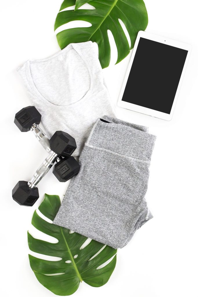 large green leaves in the background with a table, dumbell weights and work out clothes