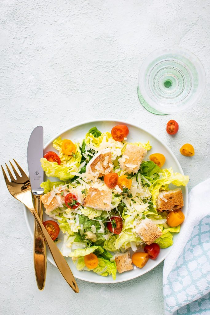 A caeser salad with croutons, cheese, tomatoes and lettuce.