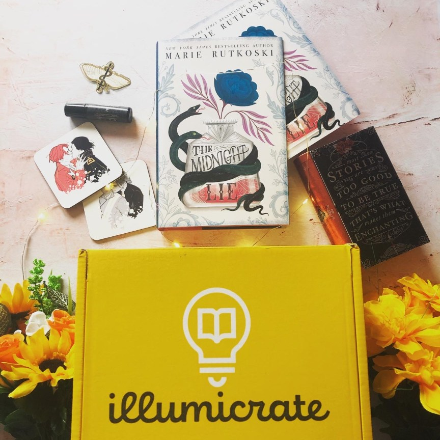 an unboxing photo of the february illumicrate book box subscription which includes all the items above the yellow illumicrate box on a pink background. the items pictured include a serpent and dove bookmark clip, a book called the midnight lie, a rollerball perfume by madame alchemie, two coasters featuring the couples from a darker shade of magic, a book shaped tin with a quote from the book stalking jack the ripper.