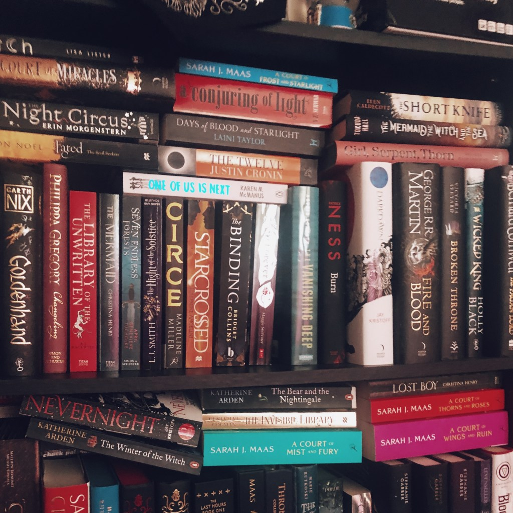 a picture of a black bookshelf full of books, mostly fantasy.