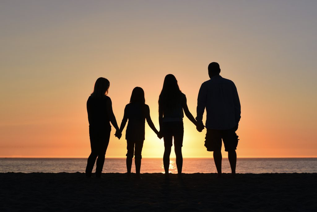 a family standing together outside holding hands and looking into the sunset