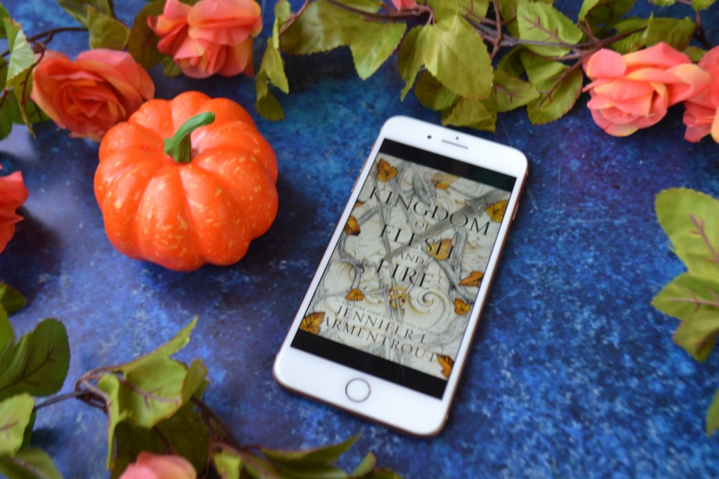 blue background with a pumpkin and iphone. the book cover for a kingdom of flesh and fire is visible on the screen of the phone.