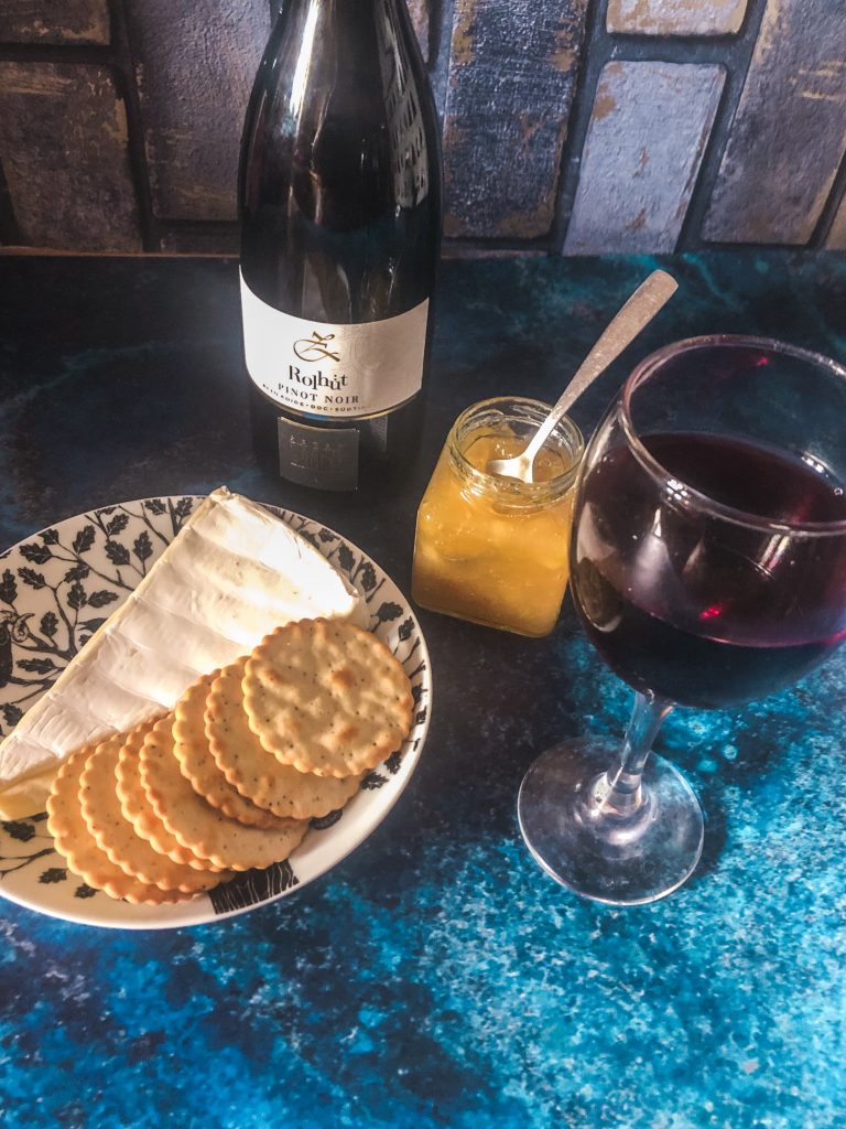 a bottle of Pinot Noir Rolhüt 2018 italian red wine next to a pot of fruit chutney, a plate of cheese and crackers and a full glass of red wine.