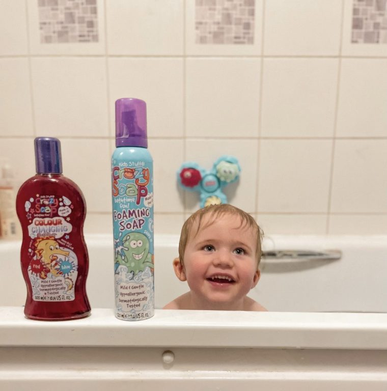 A smiling toddler in the bath with some Kids Stuff Crazy Bathtime products on the side. These include colour changing bubble bath and moldable foam soap.