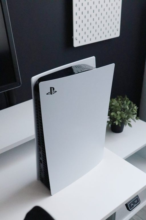 An upright PS5 on a white surface