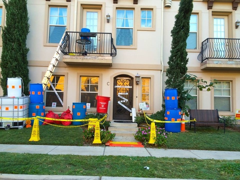"""Near Highland Park High School, a townhome has been decorated with HazMat bins and """"Caution"""" tape, lampooning our recent Ebola scare."""