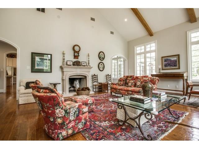 Vaulted den with fireplace and tall windowsoverlooking back of p