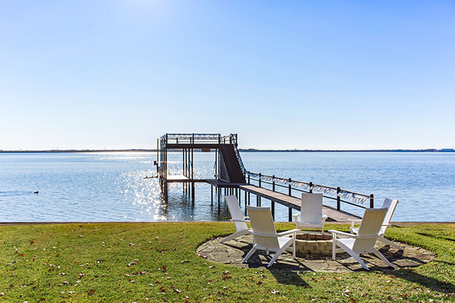 Panoramic lake views and a private boat house highlight outside amenities.