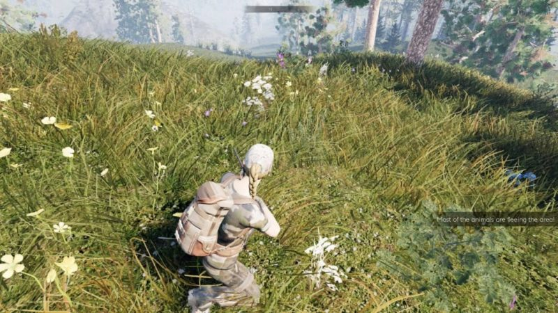 Blonde woman kneeling with a gun in grassy area.