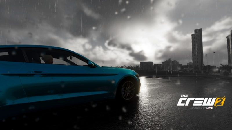 Blue sports car driving in the rain, downtown area in background.