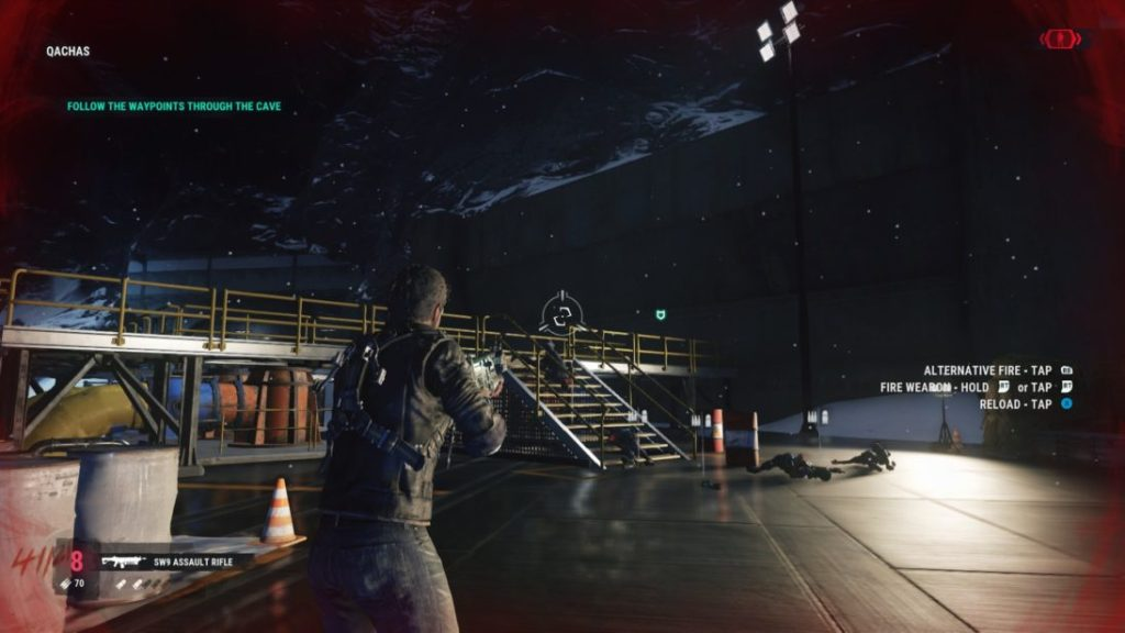Rico engaged in combat at enemy base. Red rimmed screen indicating that he is taking damage.