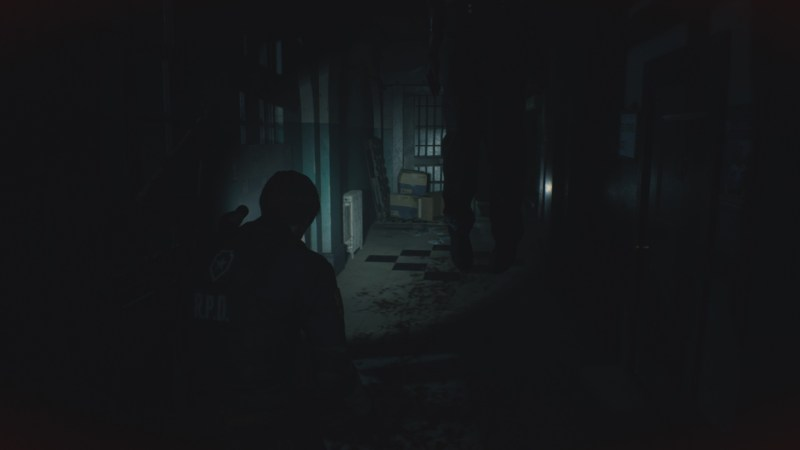 Player character walking down dark hallway with enemy hanging from the ceiling above him..