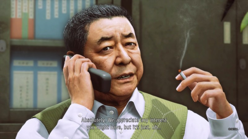 Cutscene with NPS on the phone wearing a white shirt, white subtitles displayed over the shirt.