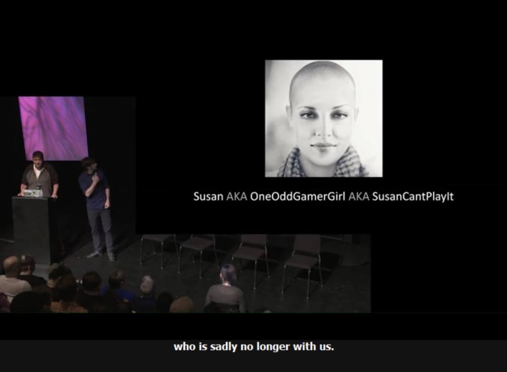 Screenshot of Ian Hamilton's memorial bit for Susan at GAConf 2019, showing Ian at the podium, an interpreter beside him, and Susan's photo on the presentation screen.