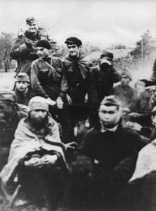 Grupa jeńców sowieckich grzejących się przy zapalonym ognisku. Niemiecki wartownik uzbrojony w karabin w płaszczu i furażerce.