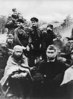 Obóz jeniecki w Szebniach - Grupa jeńców 1941-42 grzejących się przy zapalonym ognisku. Niemiecki wartownik uzbrojony w karabin w płaszczu i furażerce.