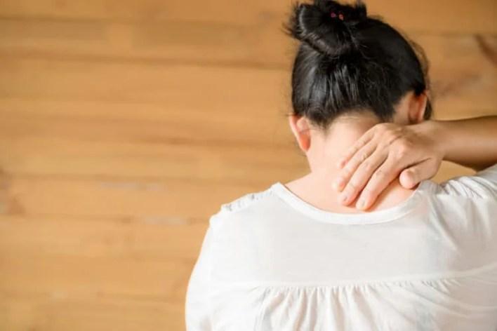 femme vue de dos qui se tient la nuque de douleur