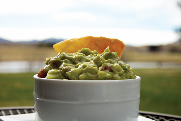 A tortilla chip is dipped into a heaping bowl of super lemon haze Mexican guacamole.