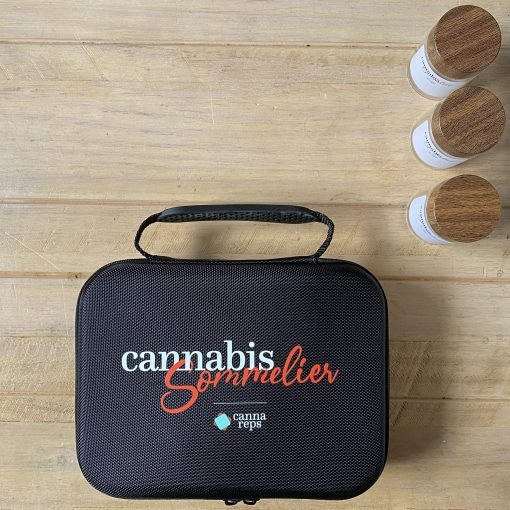 Birdseye view of a closed Cannabis Sommelier Toolkit with included glass jars standing aside