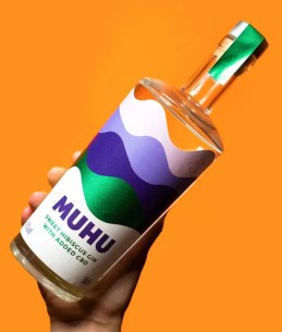 A hand holding a bottle of Muhu CBD gin against a colourful background