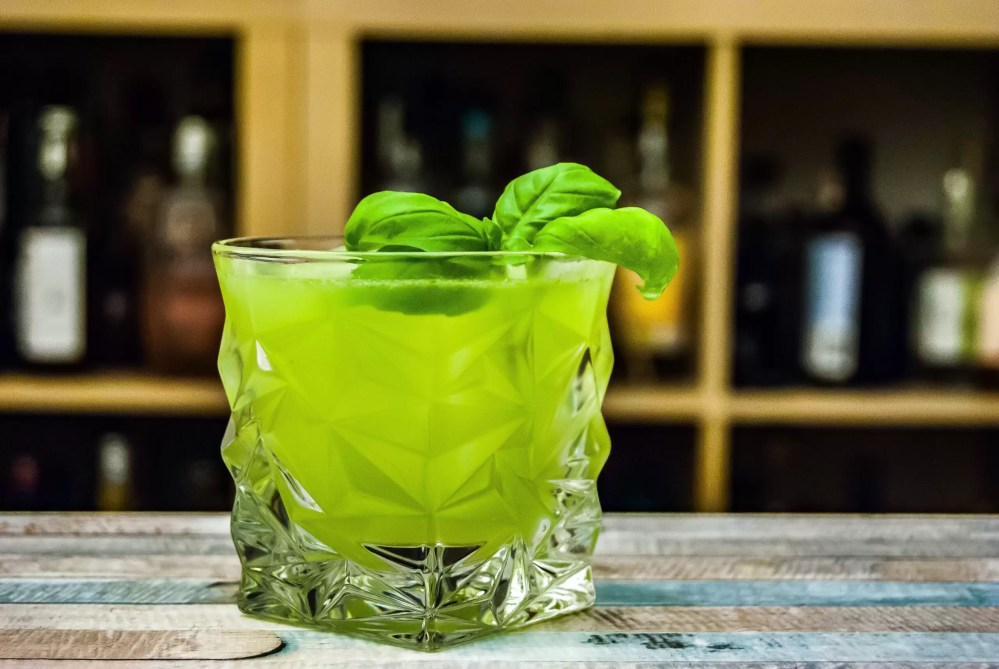 A green cocktail in a short glass with a spring of basil in it