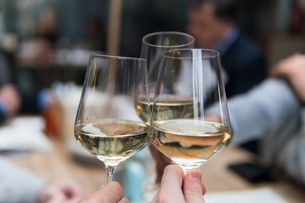Three people clinking three glasses containing white wine
