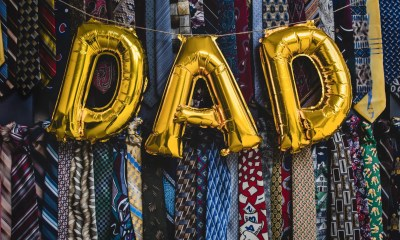 Balloons spell out DAD hang over a selection of men's ties