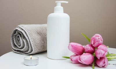 A light brown towel rolled up next to a white lotion bottle. There is a small night light and pink rose on other side of the lotion