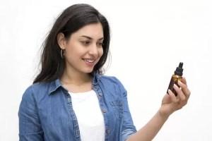 brown haired women holding a CBD oil bottle